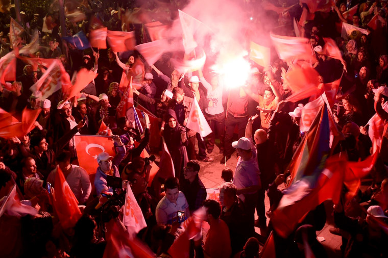Image: Supporters of Turkey's president wave flags and brandish smoke bombs during a rally after the initial results of a nationwide referendum.