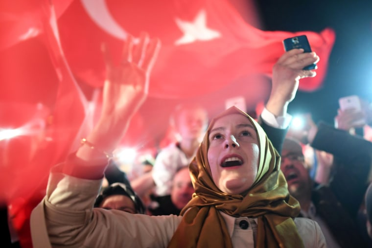 """Image: A woman flashes a four finger sign called """"the rabia sign"""" as she celebrates and waits to greet the Turkish president when he arrives for his speech in Istanbul, April 16."""