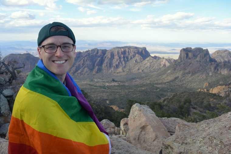 Mikah Meyers on top of Emory Peak, the highest point in Big Bend Nat Park with rainbow flag.