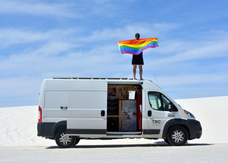 Mikah Meyer standing on top of his van with rainbow flag at White Sand National Monument in New Mexico