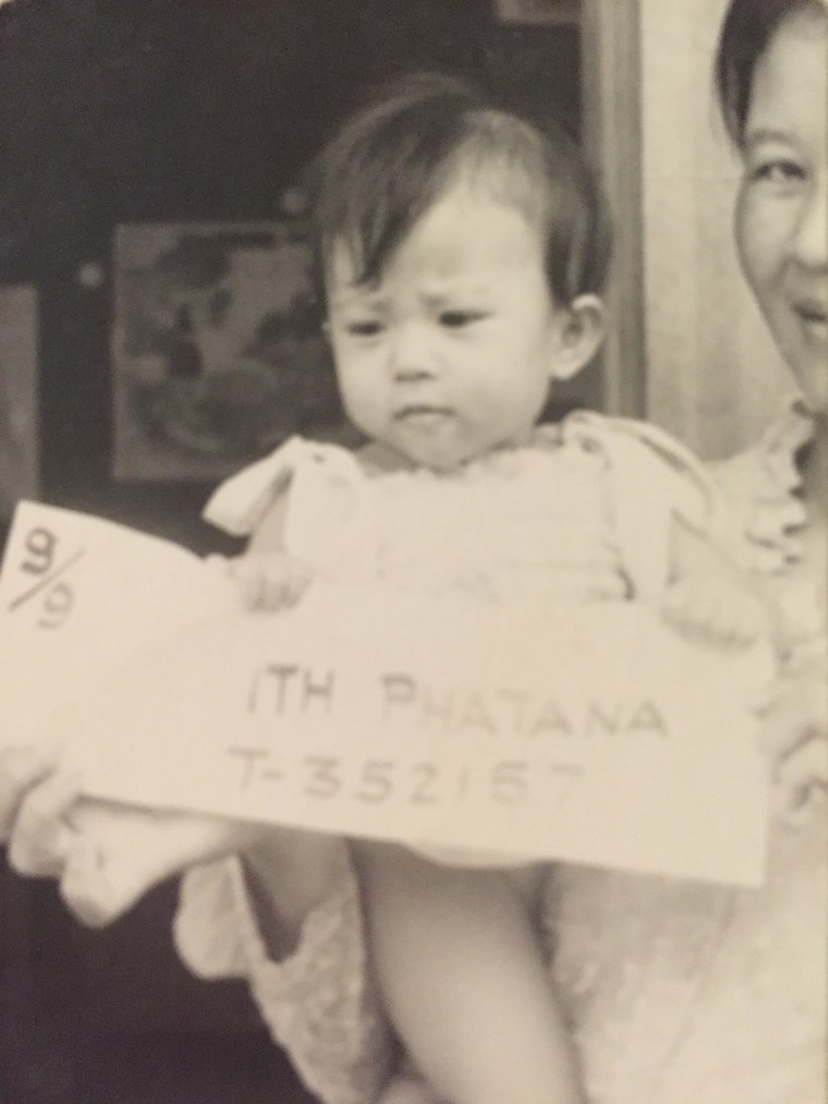 "Phatana Ith at 7 months old in Cambodia. The serial numbers were used to identify the Ith family. The number ""9/9"" indicates that Itm was the youngest of the nine in her party."