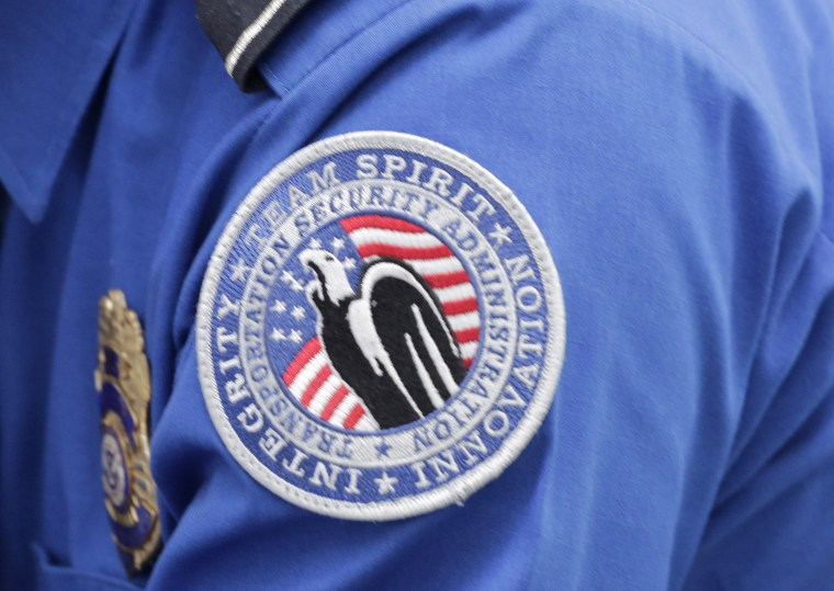 Image: A TSA shoulder patch is shown on the uniform of a Transportation  Security Administration officer