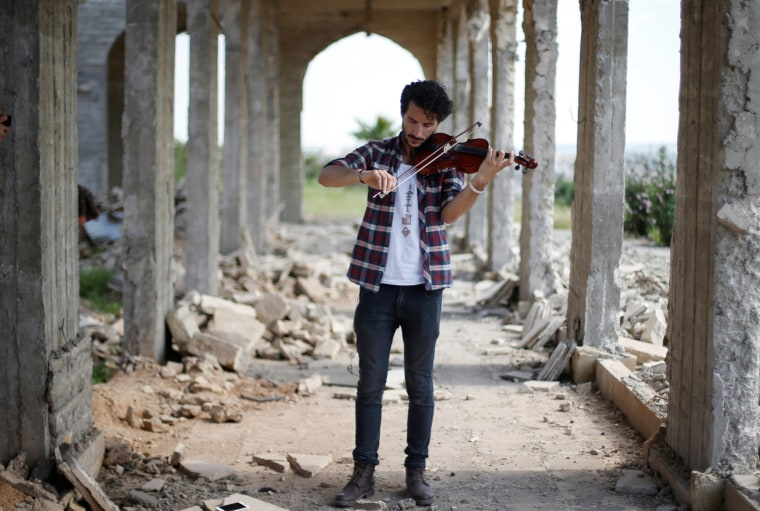 Image: Ameen Mukdad, a violinist from Mosul who lived under ISIS's rule for two and a half years where they destroyed his musical instruments, performs in eastern Mosul