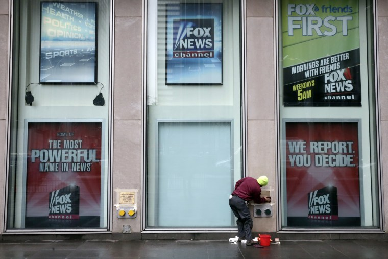 Image: A worker cleans a sign outside the Fox television studios