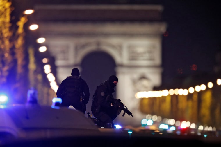 Image: Masked police stand on top of their vehicle on the Champs Elysees Avenue after a shooting incident in Paris
