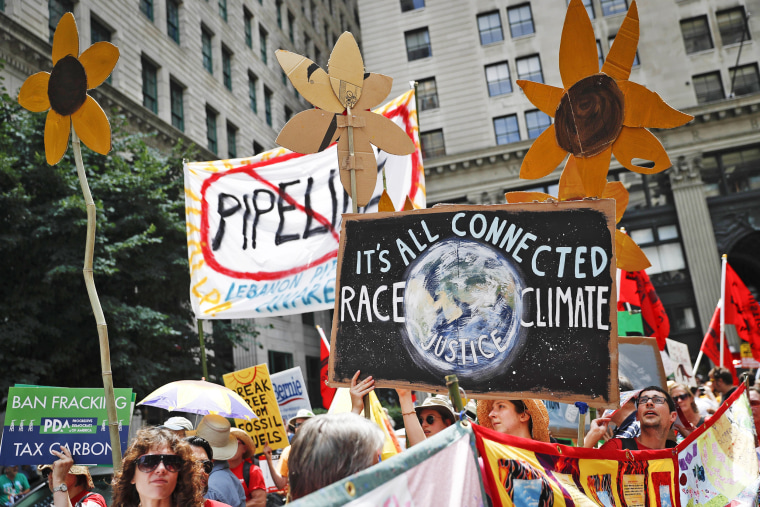 Image: Climate change activists carry signs as they march during a protest in downtown in Philadelphia