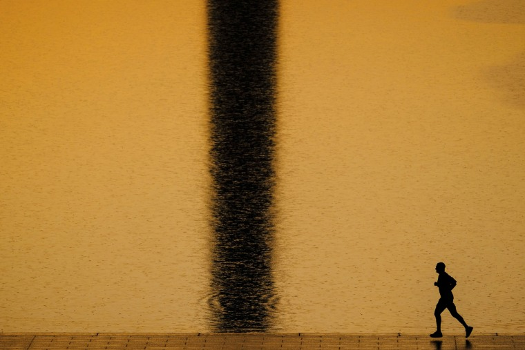 Image: An early morning runner passes the shadow of the Washington Monument