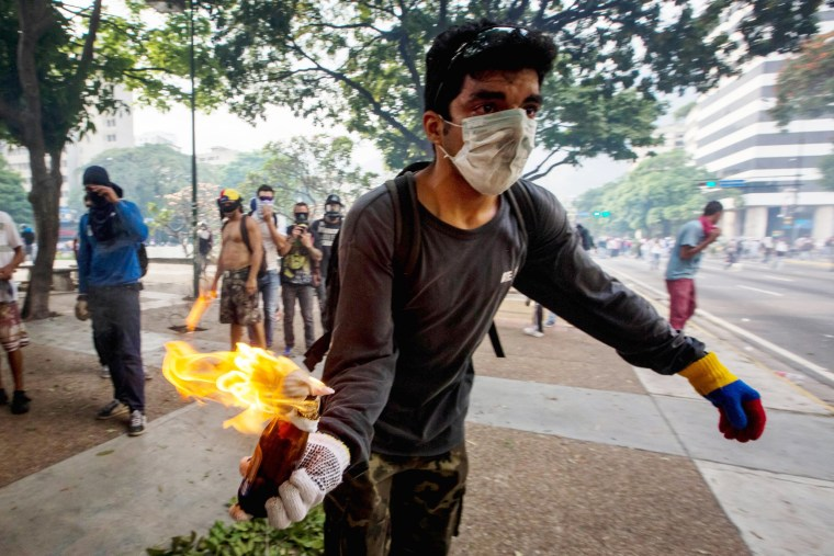 Image: A demonstrator holds a Molotov cocktail during clashes with police during protests in Caraca