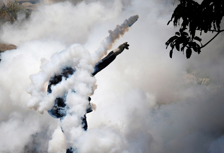 Image: A demonstrator throws back a tear gas grenade while clashing with riot police in Caracas