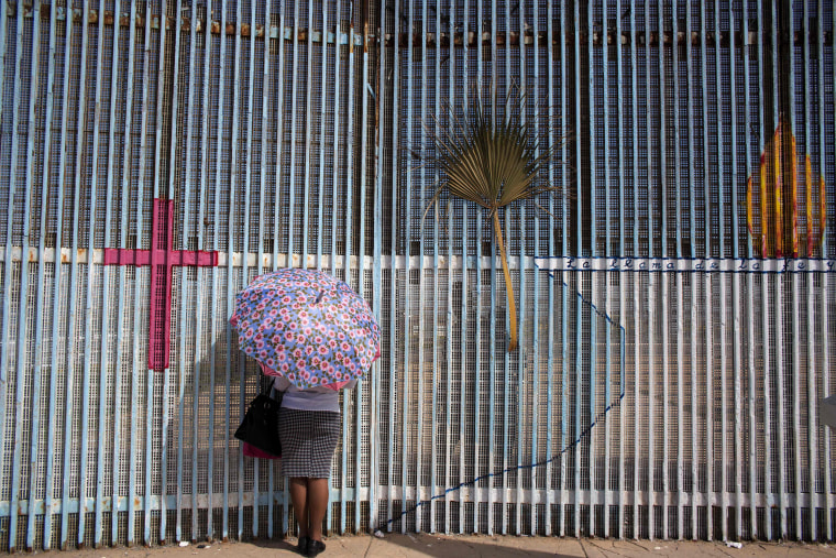 Image: A woman talks to a relative through the border fence