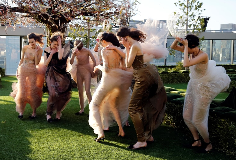 Image: Models struggle against strong wind before the rehearsal of Christian Dior's Haute Couture Spring-Summer 2017 live show to celebrate Dior's new flagship store at the rooftop of Ginza Six mall in Tokyo