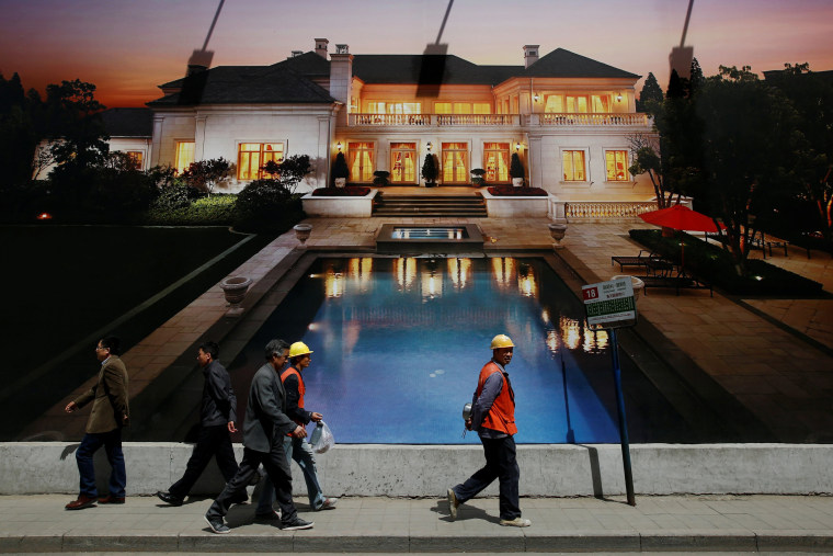 Image: People walk past an advertising poster for a luxury villa, outside a construction site in Beijing