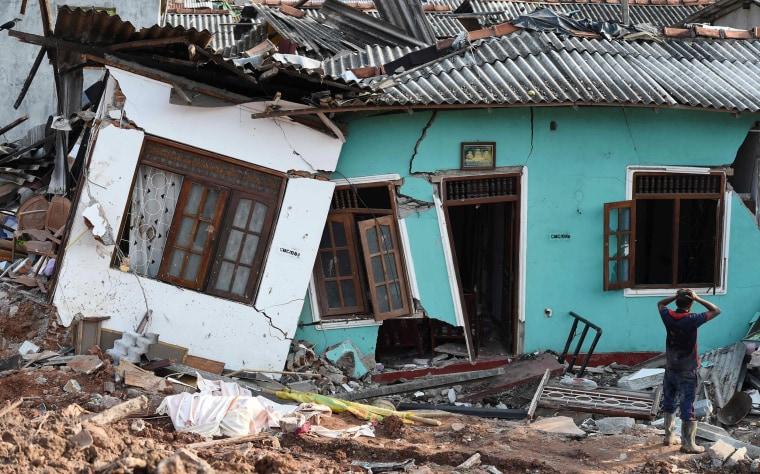 Image: A Sri Lankan resident walks through damaged homes