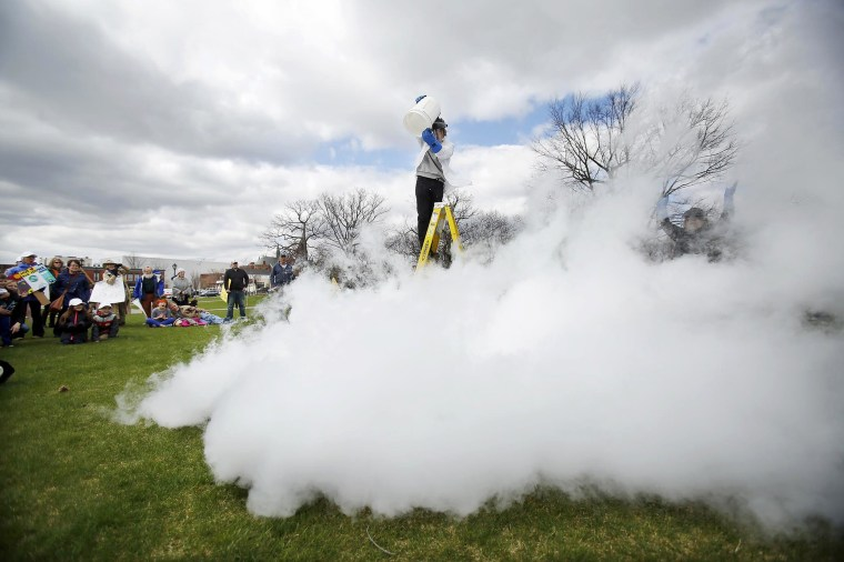 "Image: Harry Park pours boiling water into a bucket of liquid nitrogen, making a ""thunder cloud"" for a science experiment demonstration by the Berkshire Museum at the Pittsfield March for Science in Pittsfield, Massachusetts."