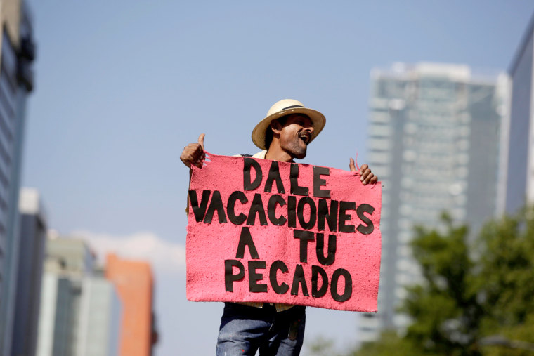 "Image: A demonstrator holds a placard as he participates in the March for Science rally in Mexico City, Mexico. The placard reads ""Give holiday to your sin."""