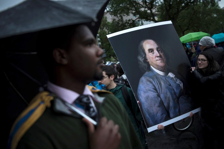 Image: Activists carry a portrait of Benjamin Franklin-- an American Founding Father and renowned scientist-- during a march in Washington, DC.