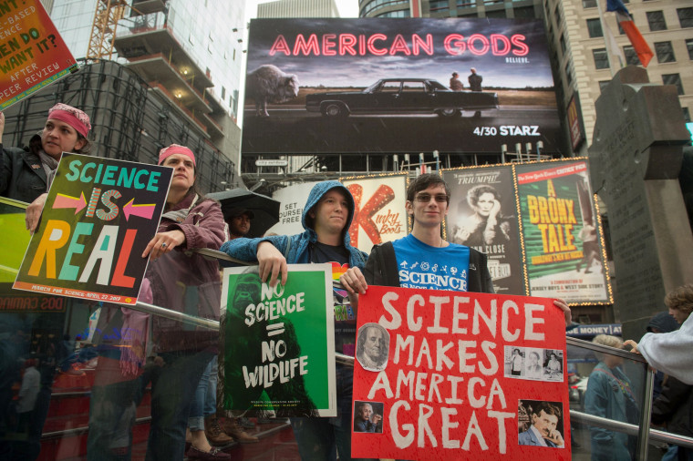 Image: People stand with signs in Times Square at the end of the March for Science in New York.