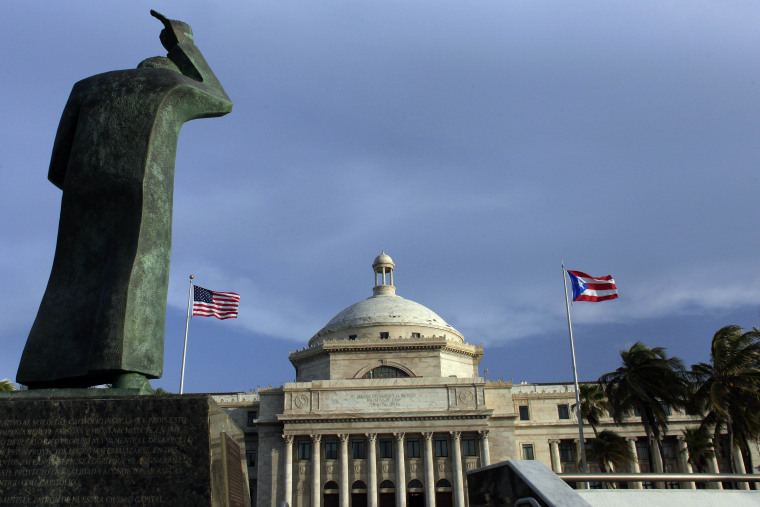In this July 29, 2015 file photo, a bronze statue of San Juan Bautista stands in front of Puerto Rico's capitol flanked by U.S. and Puerto Rican flags, in San Juan.