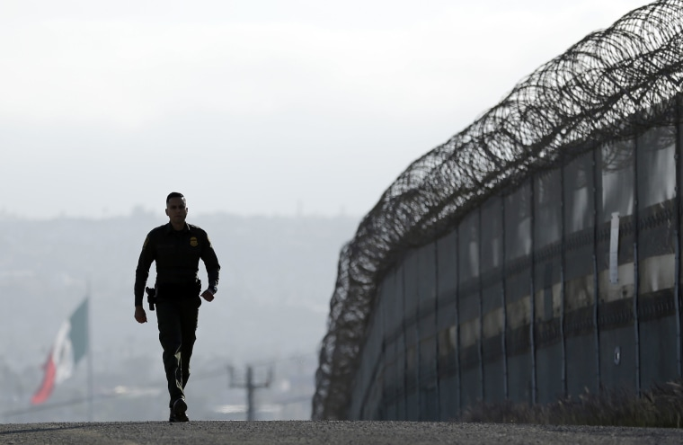 Image: A Border Patrol agent walks near a fence in San Diego
