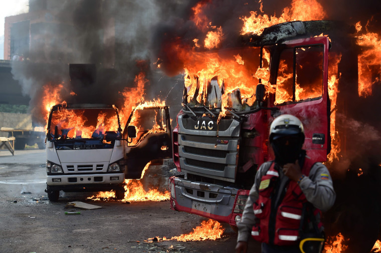 Image: Trucks burn in flames during a demonstration in Caracas