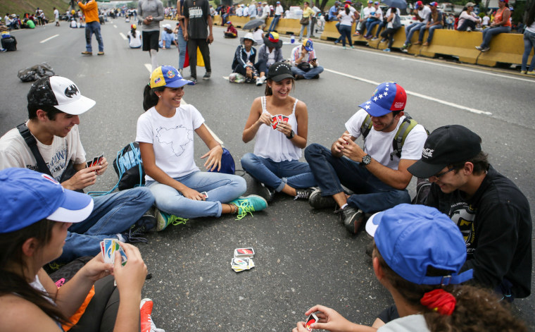 Image: A group of people play cards during a sit-in in Caracas