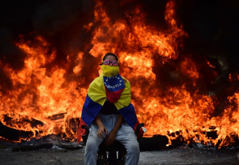 Image: An activist sits in front of a burning barricade