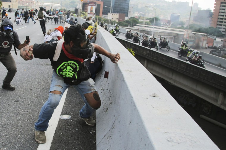 Image: Anti-government protesters throw stones from a highway overpass at a passing police patrol in Caracas