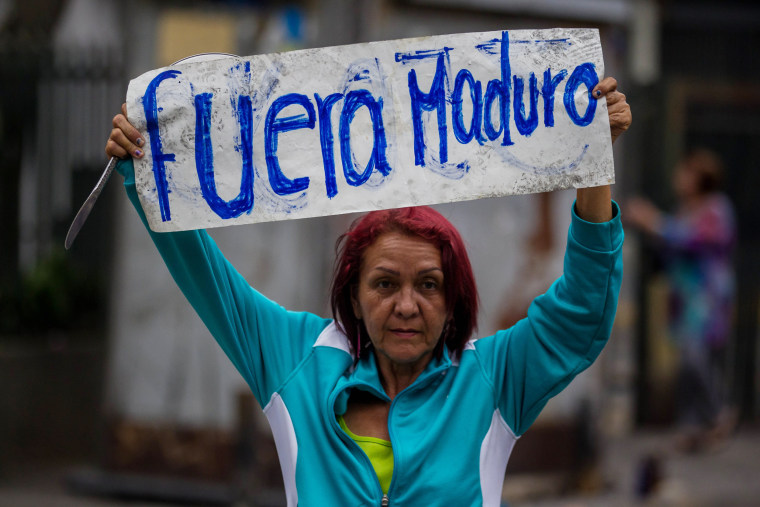 """Image: A demonstrator holds a banner that reads, \""""Maduro Out\"""" during a demonstration in Caracas"""
