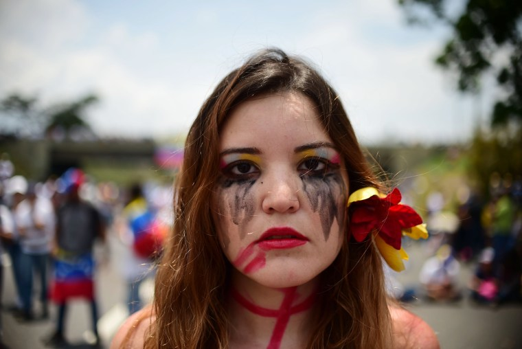 Image: An opposition activist participates in a sit-in in Caracas