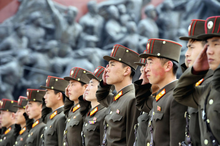 Image: North Korean soldiers salute bronze statues of North Korea's late founder Kim Il-sung and late leader Kim Jong Il at Mansudae in Pyongyang
