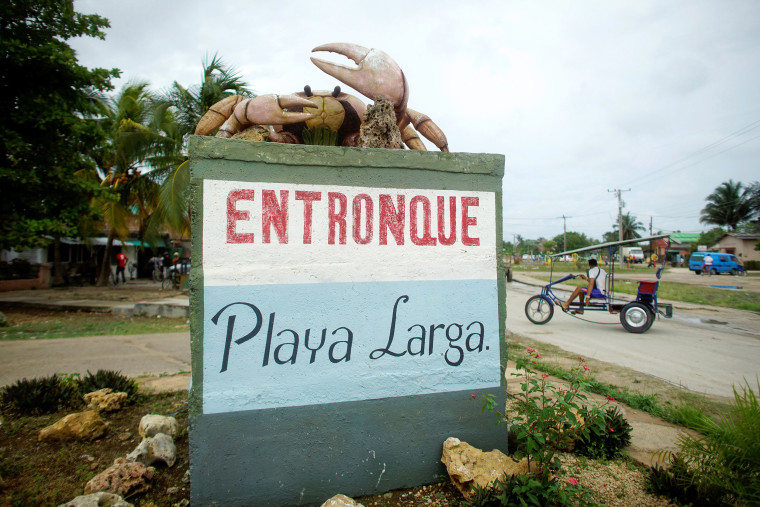 Image: A giant crab monument is seen over a sign at the entrance of Playa Larga, Cuba