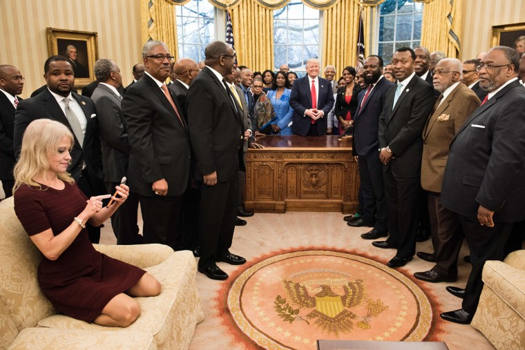 Image: Kellyanne Conway (L) checks her phone after taking a photo