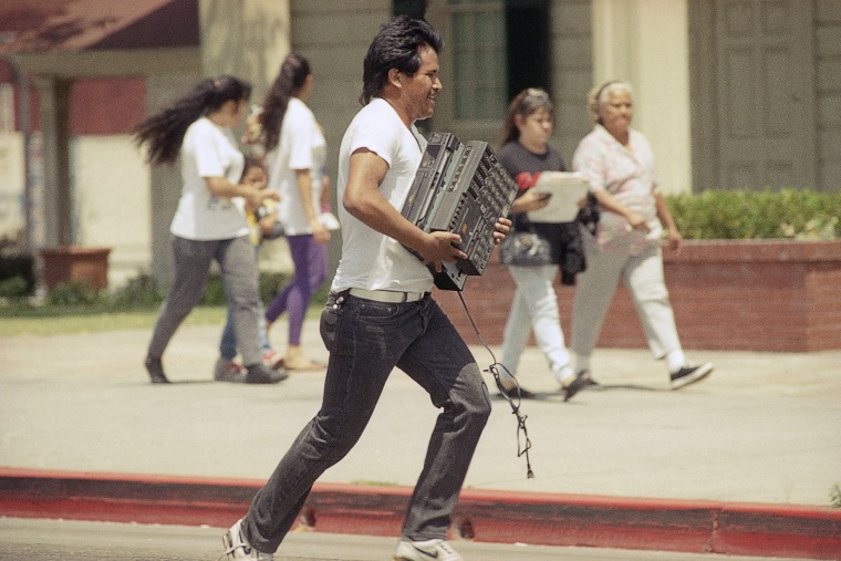 An unidentified man runs down Vermont Street in Los Angeles on Thursday, April 30, 1992 with electronic appliances taken from a 3rd Street store. Looting and fires continue in the wake of the verdicts from the Rodney King beating trial handed down.