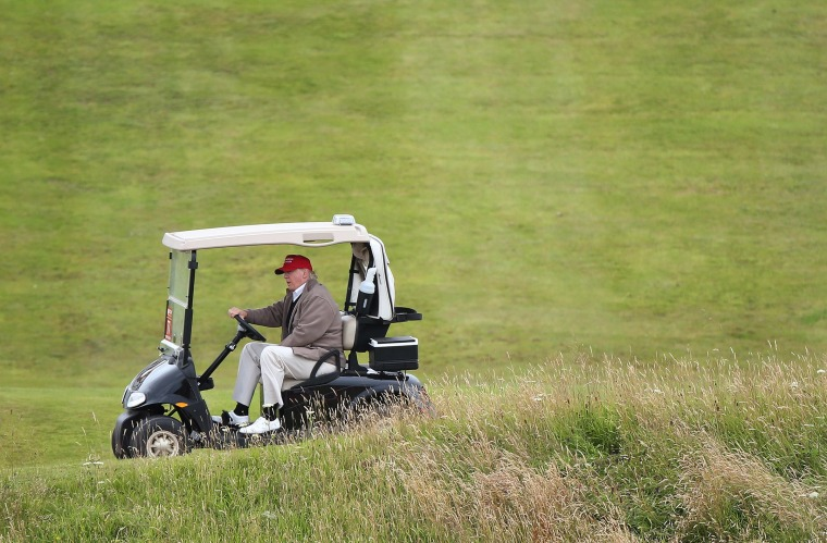 Image: Donald Trump, who says he missses driving in his new job, is seen at the wheel of a golf buggy on his resort in Turnberry, Scotland.