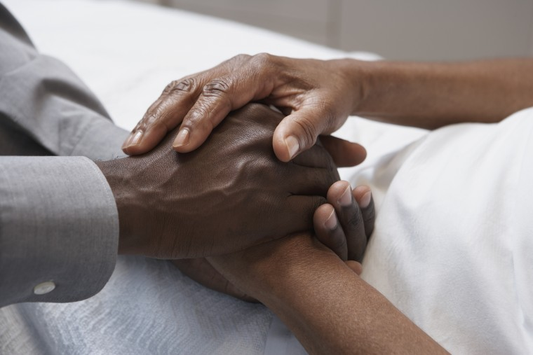 Image: Close up of African man holding hands in hospital