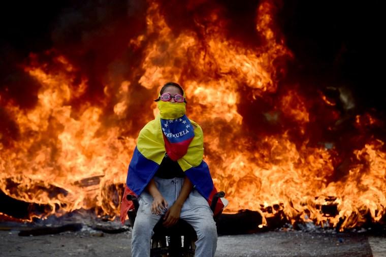 Image: A Venezuelan Opposition Activist Sits Near a Burning Barricade