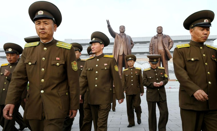 Image: North Korean Soldiers Walk in Front of Bronze Statues of North Korea's Late Founder Kim Il-sung and Late Leader Kim Jong Il