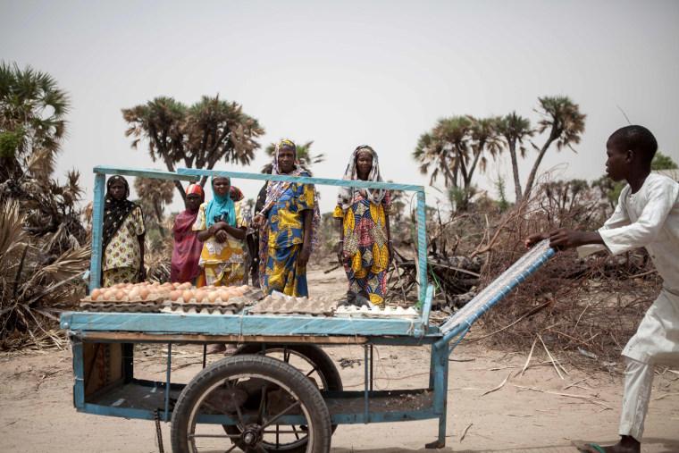 Image: A Boiled Egg Vendor Walks Past Women