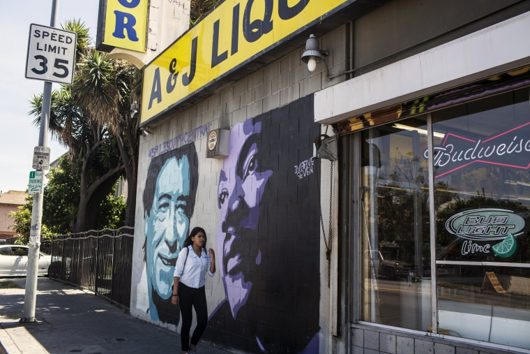 Image: A woman walks past a mural of Cesar Chavez, left, and Martin Luther King Jr., in South Central Los Angeles