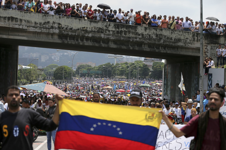 Image: Anti-government protesters block a highway in Caracas