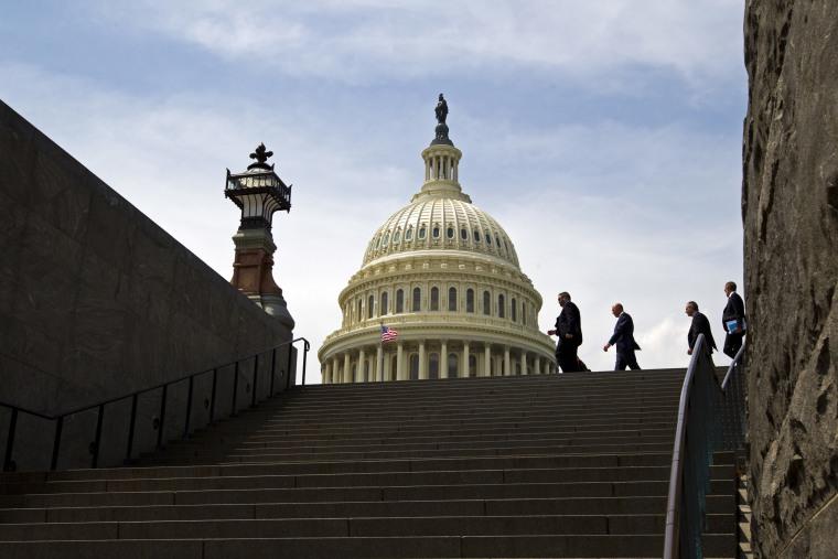 Image: People walk outside of the U.S. Capitol in Washington