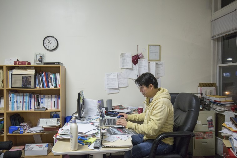 Myong Sool Chang, founder of Boston Korea, works at his desk in the weekly newspaper's Allston office. Chang started the newspaper in 2005, working alone full-time and using his credit card to get by. These days, he works with a staff of five.