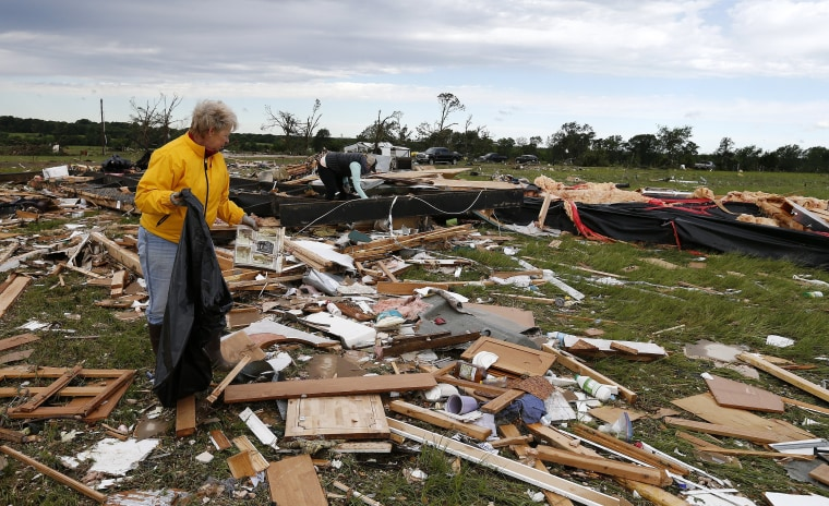 Image: Two women retrieve items for their neighbor  in Canton