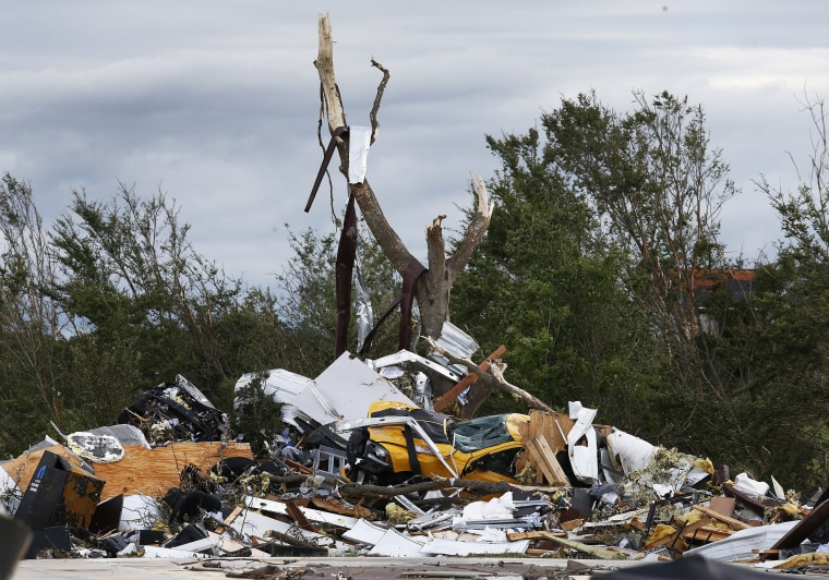 Image: Cars and damaged material is seen piled up at a local car dealership near Canton