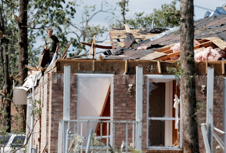 Image: A homeowner takes stock of the damage to his home after a tornado hit the town of Emory, Texas