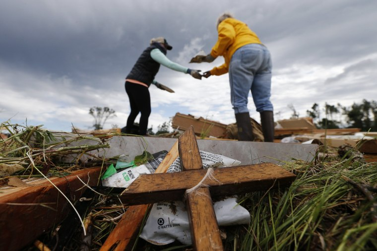 Image: Two women retrieve items for their neighbor from the remains of their trailer home