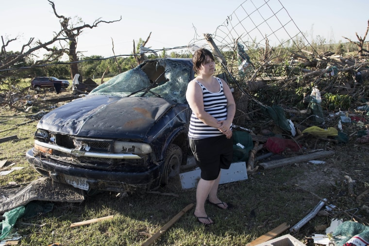 Image: Kimberly Chandler stands by her destroyed truck and debris from her home in Canton,