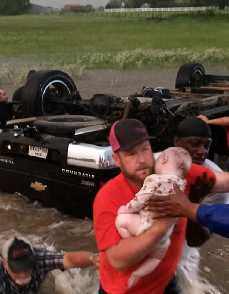 Image: A man rescues an infant that was trapped after a vehicle flipped over on a flooded highway in Canton