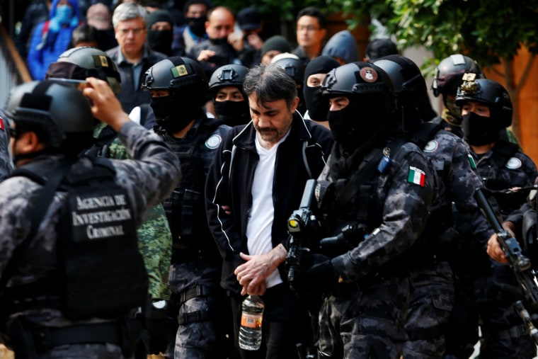 """Image: Accused drug kingpin Damaso Lopez, nicknamed """"The Graduate"""",  is escorted by police officers in Mexico City"""