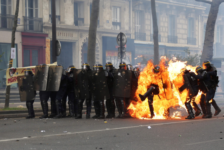 Image: French CRS anti-riot police officers are engulfed in flames